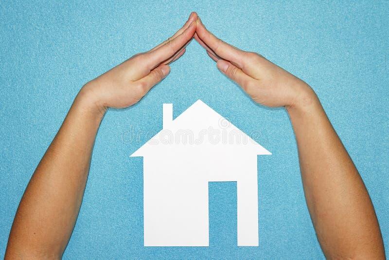 Bent u verzekerde Concept dat over witte backg wordt geïsoleerdb Dient vorm van dak over huis van Witboek op blauwe achtergrond i stock afbeeldingen
