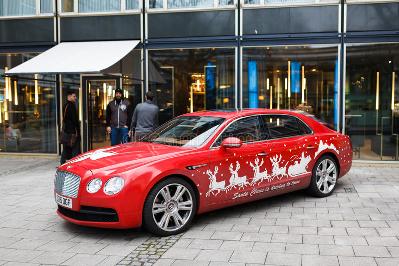 Bentley car on a street. Munich, Germany - January 02 2016: Red advertising Bentley car with inscription Santa Claus Is Driving To Town parked on a street royalty free stock image