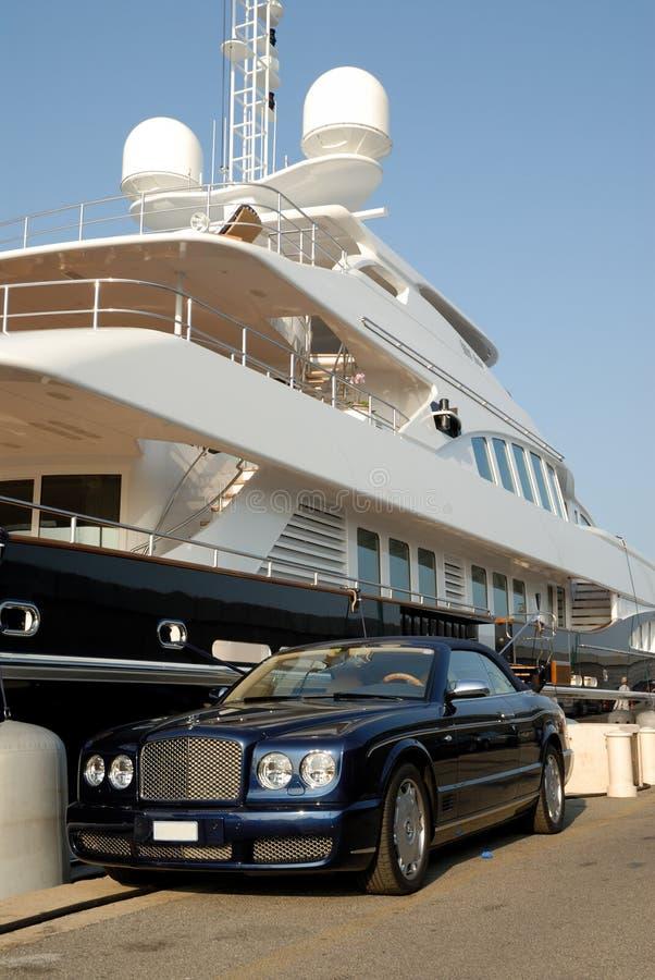 Bentley estacionou na frente de um iate luxuoso imagens de stock