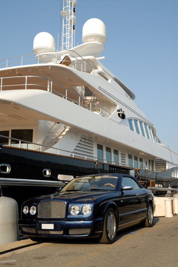 Bentley parked in front of a luxury yacht. Bentley convertible parked in front of a luxury yacht in Saint Tropez, France stock images