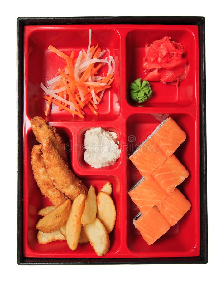 Bento lunch in the box. Set - sushi roll, salad, potato, breaded chicken, sauce and wasabi stock photography