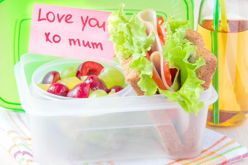 Bento lunch for your child in school, box with a healthy sandwich and fruit salad and apple juice in the bottle royalty free stock photos