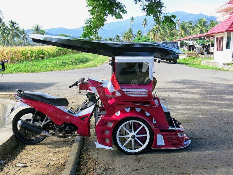 Bentor修改了用于运输人作为出租汽车的滑行车 普遍在苏拉威西岛在Kotamobag  红色摩托车 免版税库存图片