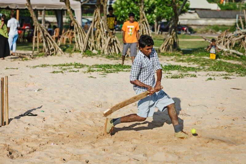 BENTOTA, SRI LANKA - APR 28: Children play cricket with bat and. Ball on sandy beach on Apr 28, 2013 in Bentota, Sri Lanka. Cricket is the most popular game in stock photos