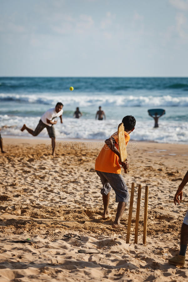 BENTOTA, SRI LANKA - APR 28: Teenagers play cricket with bat and. Ball on sandy beach on Apr 28, 2013 in Bentota, Sri Lanka. Cricket is the most popular game in stock image
