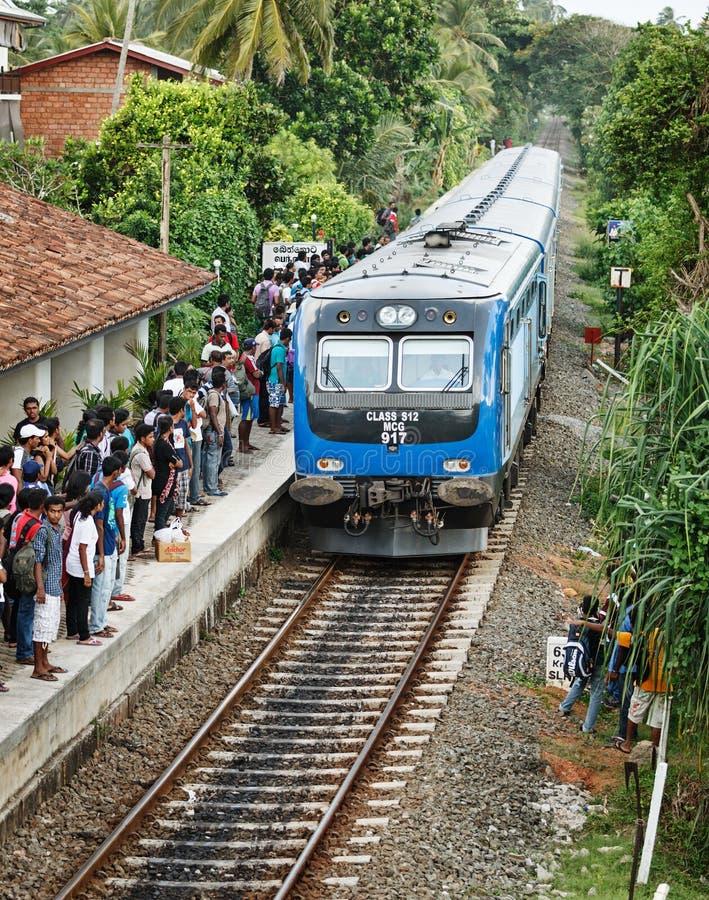 BENTOTA, SRI LANKA - 28 DE ABRIL: El tren llega para colocar con la gente imagen de archivo libre de regalías
