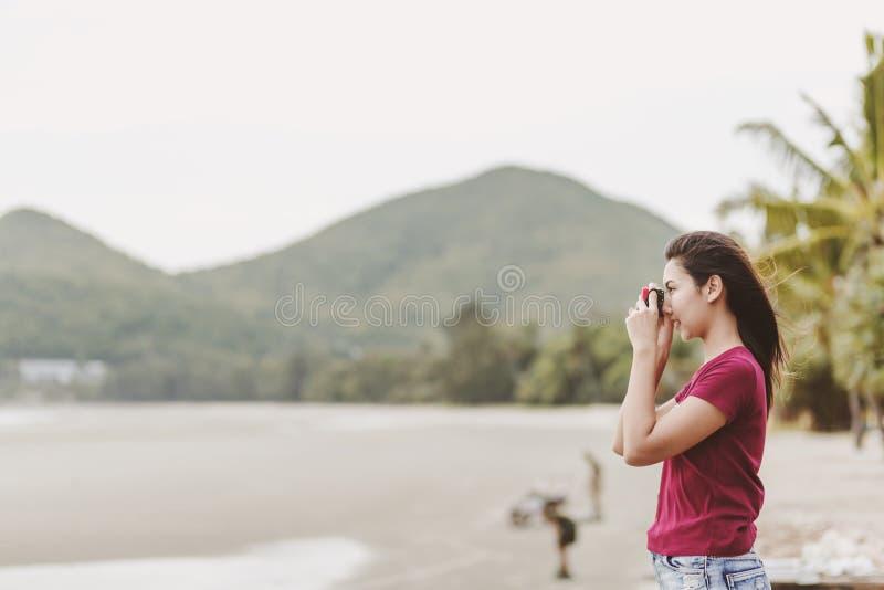 Benutzen Frauen eine Kamera zu geschossener Reise auf dem Strand lizenzfreies stockbild