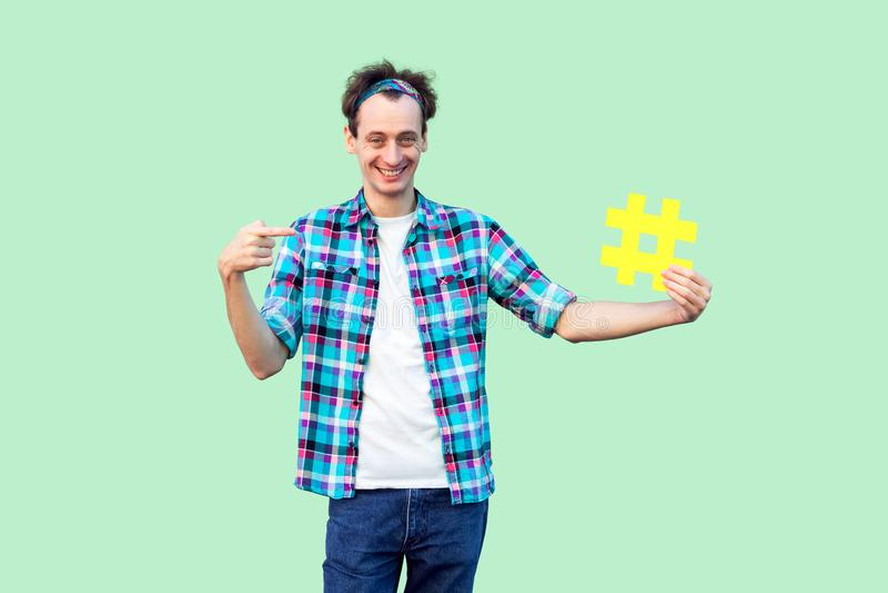 Benutzen Sie hashtag? Positiver glücklicher junger erwachsener Mann im karierten Hemd, das großes großes gelbes Haschumbauzeichen lizenzfreies stockfoto