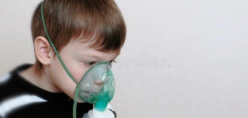 Benutzen Sie Zerstäuber und Inhalator für die Behandlung Junge, der durch Inhalatormaske inhaliert Weicher Fokus lizenzfreie stockfotos
