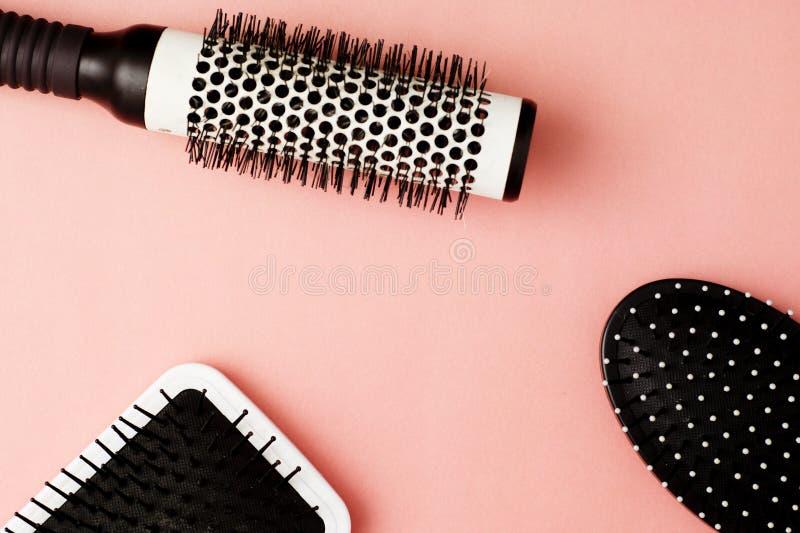 Benutzte Haarbürstenwerkzeuge auf rosa oder korallenrotem Hintergrund mit Kopienraum Schönheitsmode, Haarpflegehintergrund stockfotografie