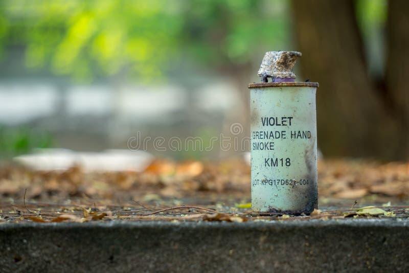 Benutzte violette Rauch-Handgranate der Farbe KM-18 gesetzt auf den konkreten Boden stockfotos