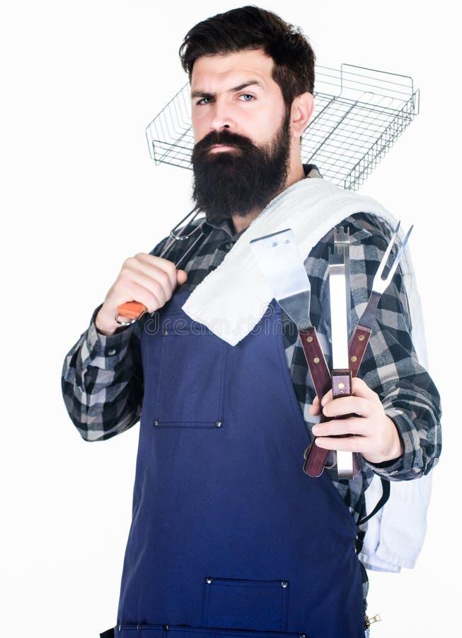 Benvenuto al mio BBQ Cuoco sicuro della griglia Tenuta barbuta dell'uomo che griglia canestro e gli strumenti per il barbecue Uso immagine stock libera da diritti