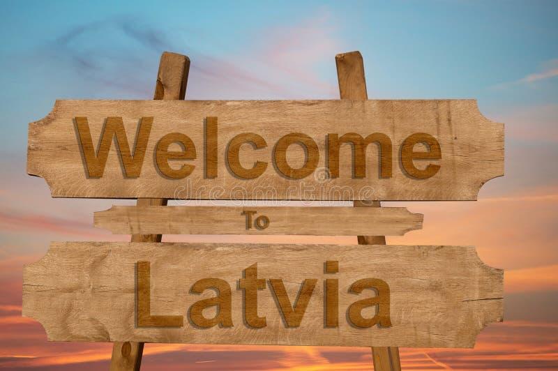 Benvenuto al segno della Lettonia su fondo di legno illustrazione di stock
