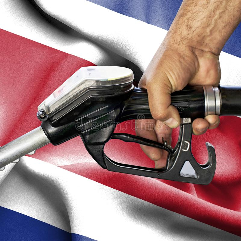 Benzyny spożycia pojęcie - Wręcza mienie węża elastycznego przeciw fladze Costa Rica obrazy stock