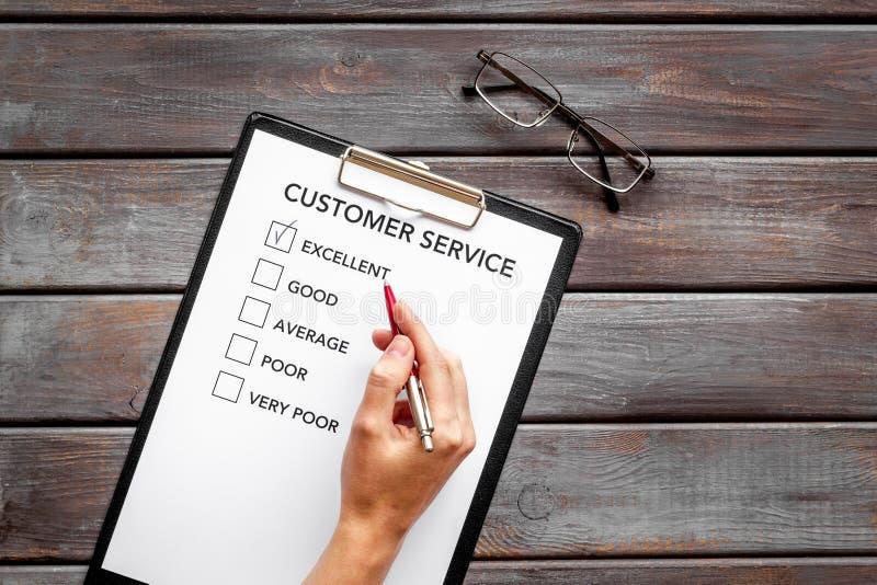 Beoordeling van de servicekwaliteit Vul klantenservicevorm met de hand op donkere houten bureaulopoleruimte stock foto