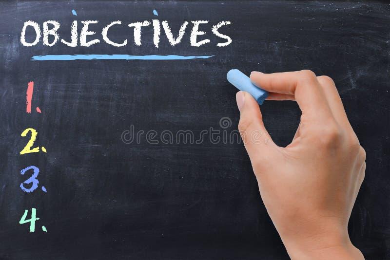 Bepaal zaken of strategische die doelstellingen door vrouw op bord worden geschreven stock fotografie