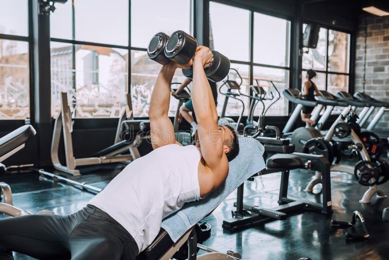 Bepaalde spiermens die en gewichtheffen uitoefenen doen bij geschiktheidsgymnastiek stock fotografie