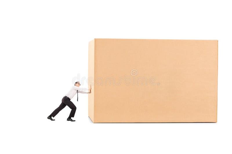 Bepaalde zakenman die een reusachtige doos duwt stock foto