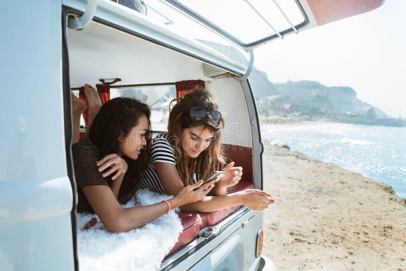 Bepaalt jonge vrouw twee greepsmartphone binnen van retro bestelwagen stock fotografie