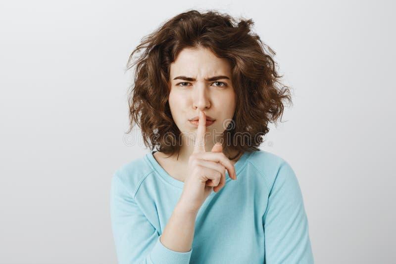 Beperk het, vertelde ik u mijn geheim Portret van unsatisfied betrokken jonge Europese vrouw met krullend haar, het fronsen stock afbeeldingen