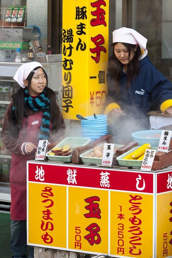 Beppu Japan - December 29, 2009: Två unga flickor som lagar mat mat på det fria, marknadsför Kokade ägg, havre och potatisar är p royaltyfria bilder