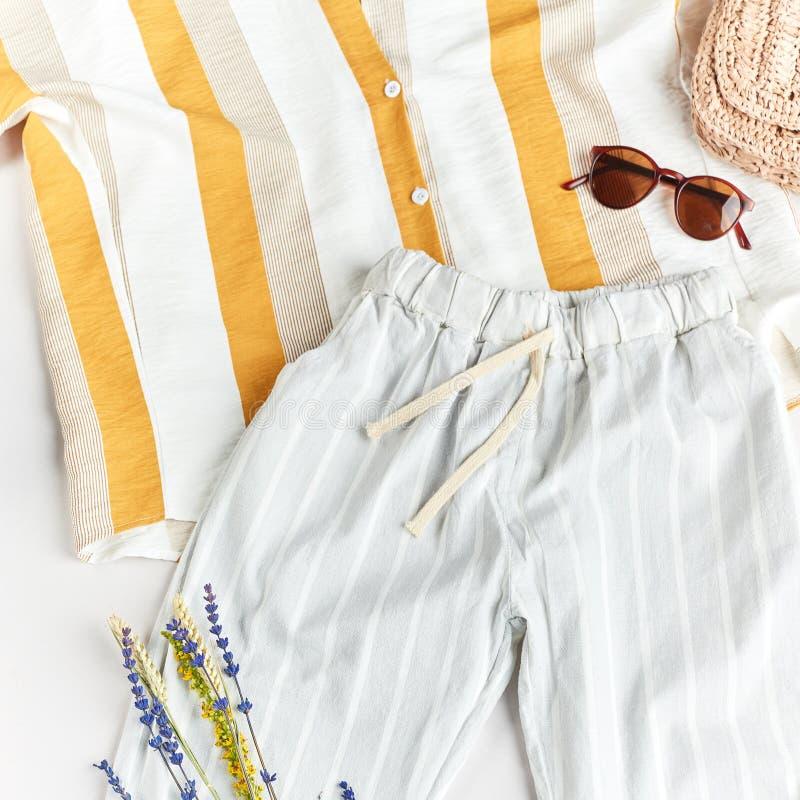 Bequeme gestreifte Bluse, blaue Hosen, Strohhut, Sonnenbrille und Blumen lizenzfreies stockfoto