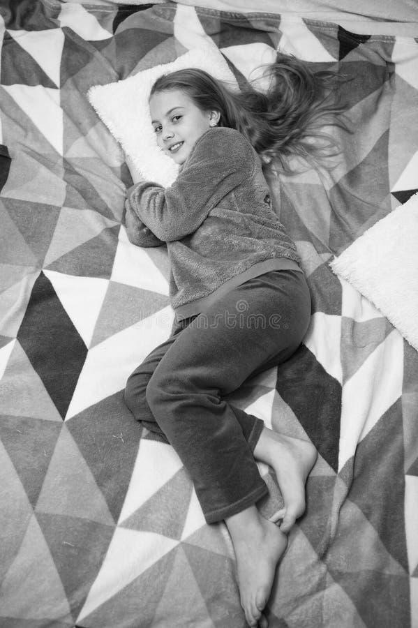 Bequeme Pyjamas f?r entspannen sich M?dchenkleinkind tragen weiche nette Pyjamas bei der Entspannung auf Bett Spielerisches entsp stockbild