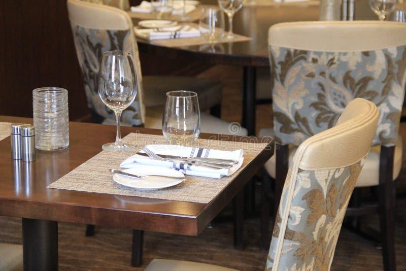 Bequeme Stühle und Gedecke im hochwertigen Restaurant stockbild