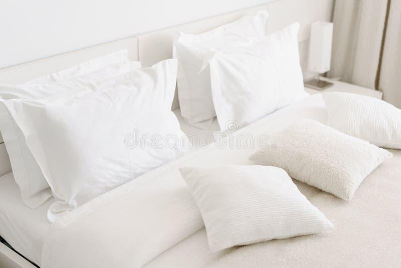 Bequeme weiche Kissen auf dem Bett Weiße Bettwäscheblätter und -kissen der Nahaufnahme auf hellem Wandraumhintergrund Frisches Be stockfotografie