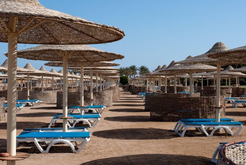 Bequemer Küstenplatz mit Strandschirmen und Strandaufenthaltsräumen stockbilder