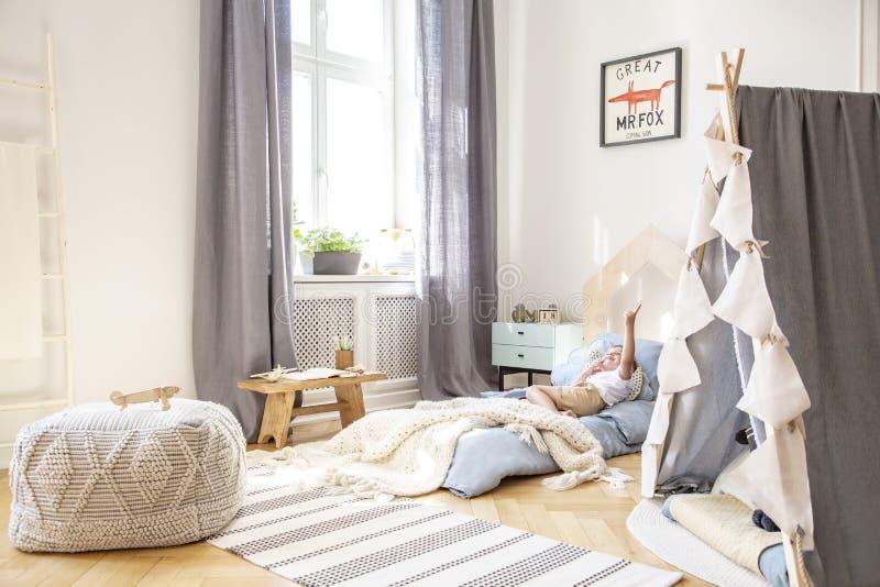 Bequemes Bett im skandinavischen Kinderschlafzimmer mit grauem Zelt und im großen Puff, wirkliches Foto mit Modell auf der Wand stockfotografie