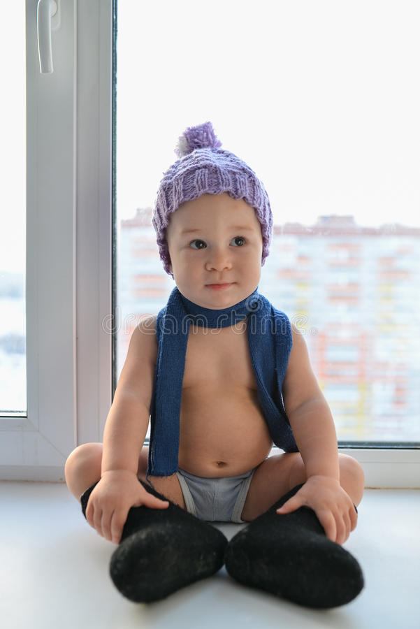 Bequemes Sitzen des sachlichen kleinen Babys nahe dem Fenster weared in der Winterkleidung stockbild