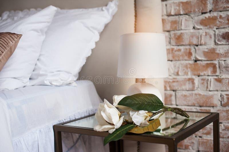 Bequemes und ruhiges Kopfende mit Lampe durch das Bett stockfoto