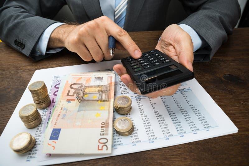 Beräknande finans för Businessperson på skrivbordet royaltyfria foton