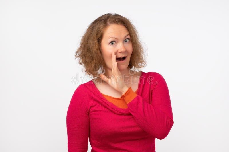 Berätta inte någon begreppet Den snacksaliga kvinnan i röd tröja säger hemlig nyheterna som ser kameran royaltyfri foto
