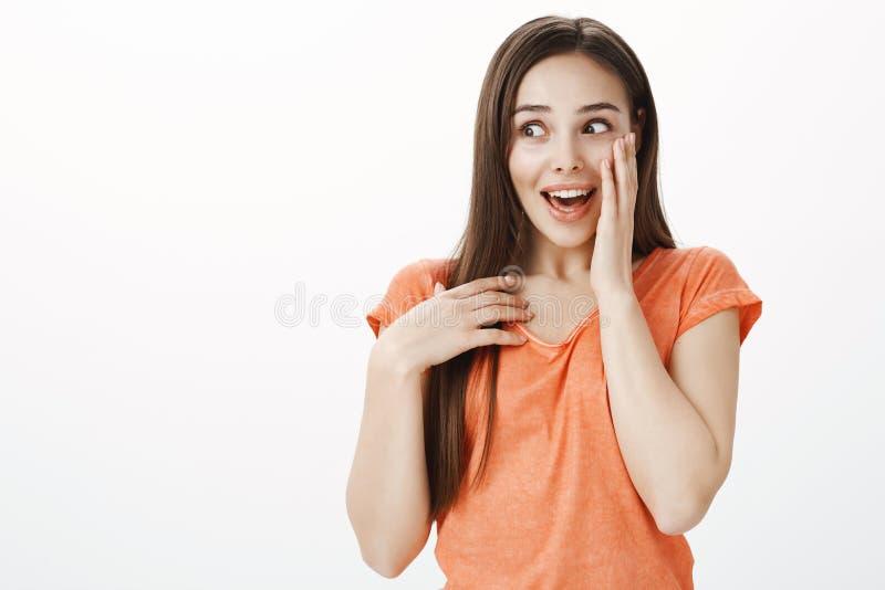 Berätta inte någon, men jag vet chockerande rykte Stående av den upphetsade snacksaliga snygga kvinnliga studenten som täcker mun arkivfoton