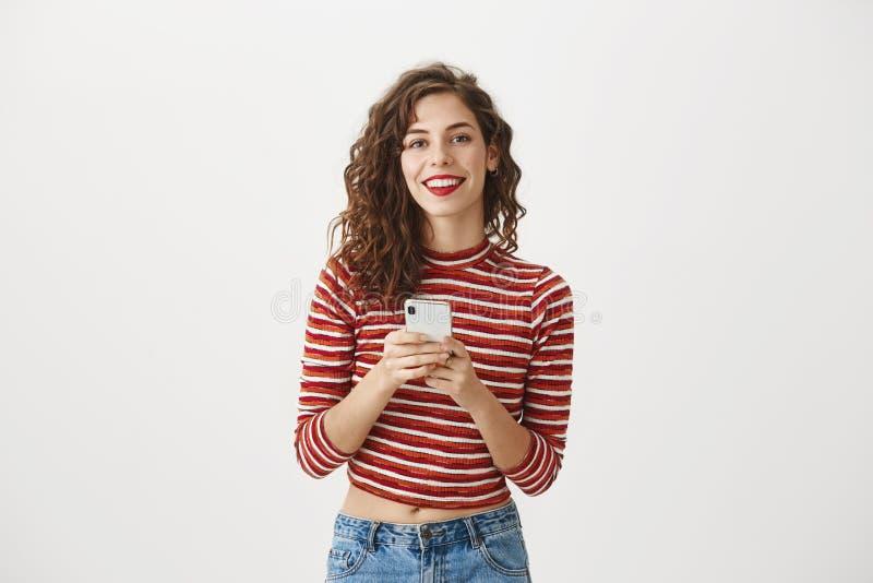Berätta mig ditt telefonnummer Studion sköt av lycklig charmig caucasian kvinna med lockigt hår och röd läppstift och att rymma royaltyfri foto