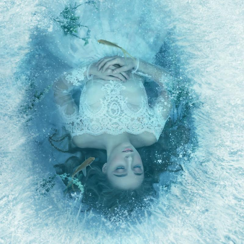 Berättelsen av en sova skönhet Flickan sover på botten av en djupfryst sjö, fisk, och havsväxt simmar arkivbilder