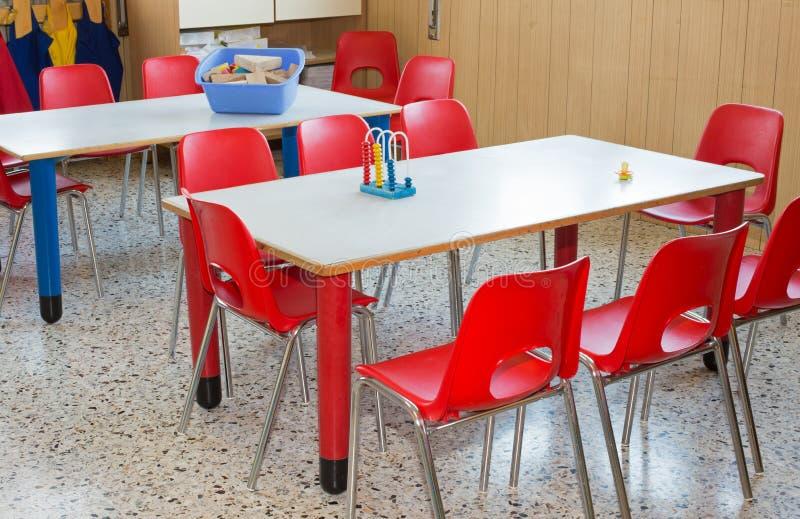 Berçário da sala de aula com cadeiras e as mesas vermelhas imagem de stock royalty free