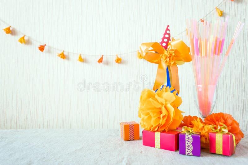 Beröm-, födelsedagpartibakgrund med den färgrika partihatten, konfettier, gåvaaskar och annan dekor arkivfoton