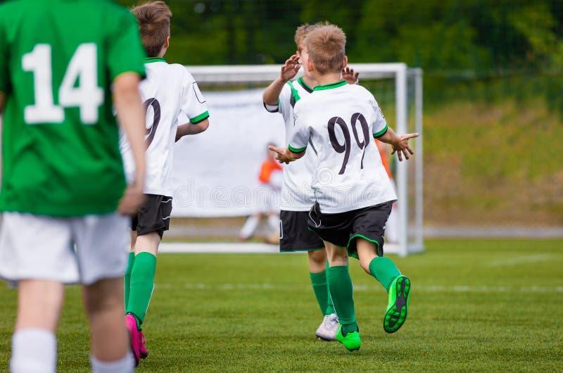 Beröm för mål för ungefotbollspelare Lyckliga barn som spelar fotbollsmatchen arkivbild