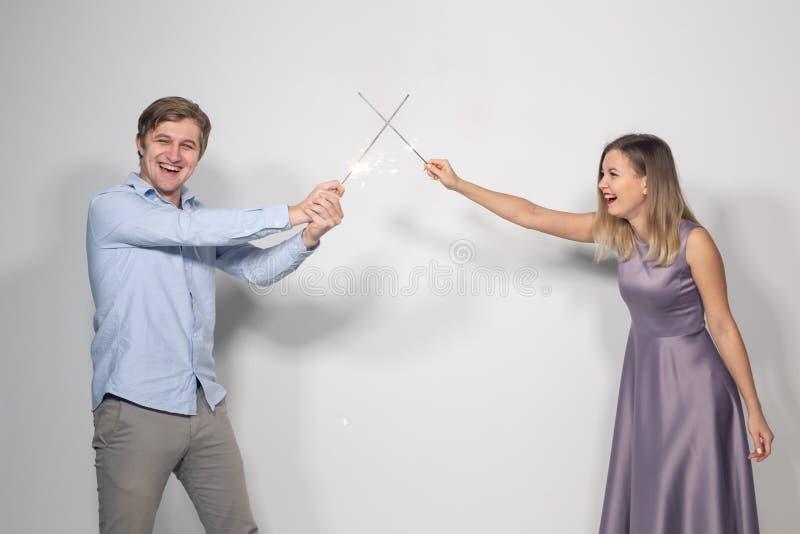 Beröm-, parti- och feriebegrepp - stående av unga par som omkring bedrar med tomtebloss royaltyfri foto