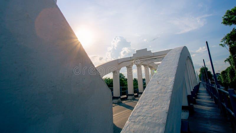Berömd bro för gammal vit av Lampang Thailand med solli för blå himmel fotografering för bildbyråer
