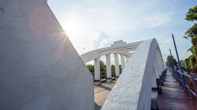 Berömd bro för gammal vit av Lampang Thailand med solli för blå himmel royaltyfri foto
