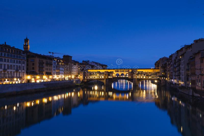 Berömd bro Ponte Vecchio på Riveret Arno i Florence, Italien ovanför ljus lugna stad clouds den mörka önskande solnedgången för s arkivbild