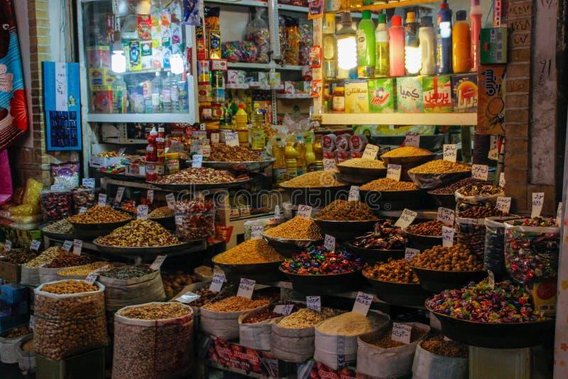 Berömd iransk marknadsbasar med torkat - frukt och sötsaker på räknaren royaltyfri foto