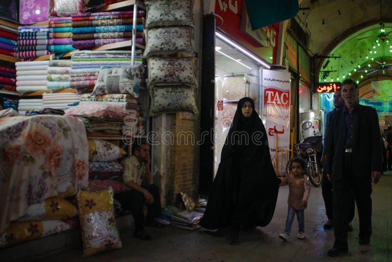 Berömd iransk marknadsbasar och en kvinna i en svart chodor som går ner en textilgata med hennes make och son royaltyfria foton