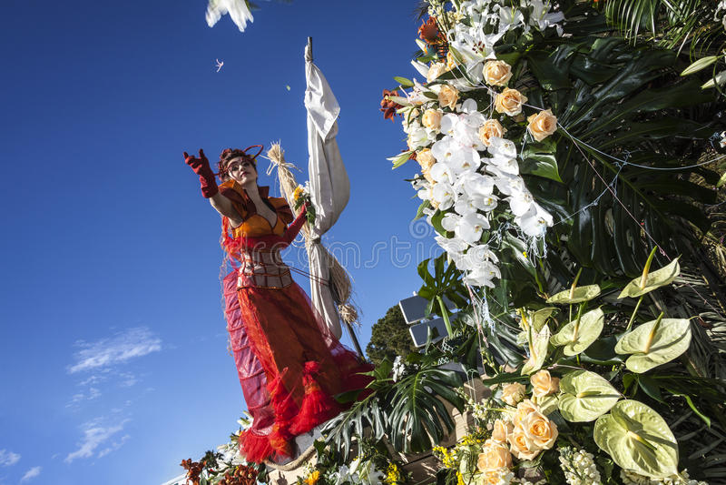 Berömd karneval av Nice, blomma`-strid En kvinnaunderhållare lanserar den vita blomman royaltyfri foto