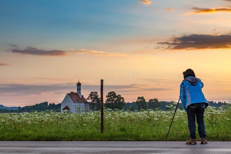 Berömd kyrka för St Coloman i härligt morgonljus med blommafältet i sommar, Bayern, Tyskland arkivfoto