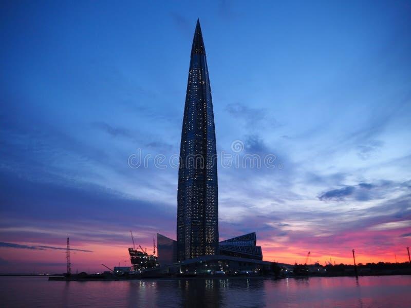 Berömd skyskrapaLakhta mitt på den härliga solnedgången Skymning mång--färgad rosa och blå himmel med färgrik reflexion i havet fotografering för bildbyråer